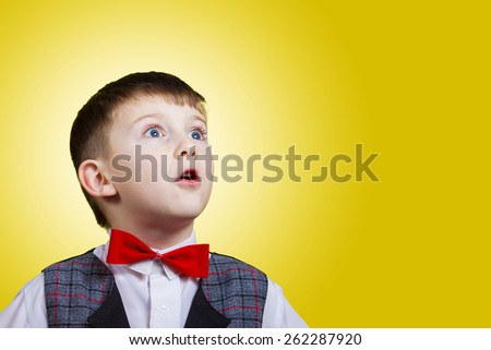 Surprised little boy looking up with mouth open isolated over yellow background. - stock photo