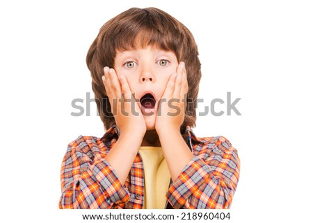 Surprised little boy. Shocked little boy keeping mouth open and touching face with hands while standing isolated on white - stock photo