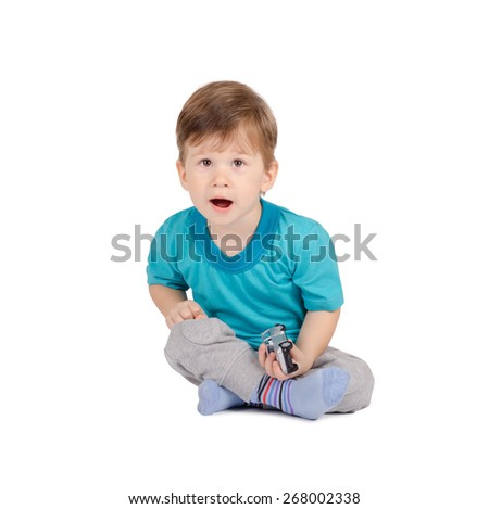 Surprised little boy with toy car sitting on the floor isolated on white background