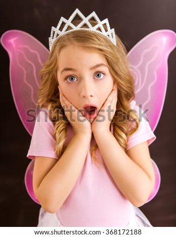Surprised little fairy with pink wings and white crown against dark background, close-up - stock photo