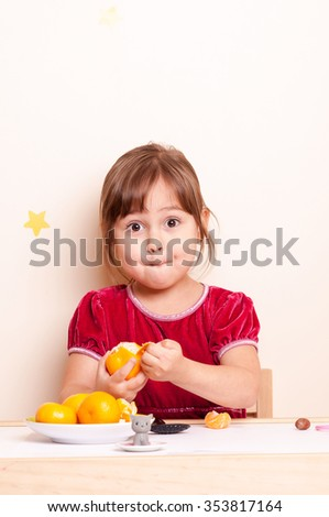 surprised little girl eating citrus - stock photo