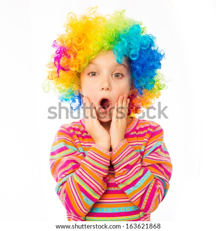 surprised little girl in clown wig isolated on white background - stock photo