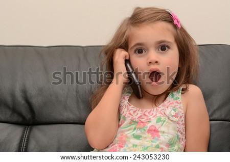 Surprised little girl speak on the phone at home. Concept photo of long distance ,call ,communication, telephone, service, overseas, conversation, technology - stock photo
