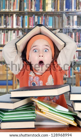 Surprised little girl with many books studying in the school - stock photo