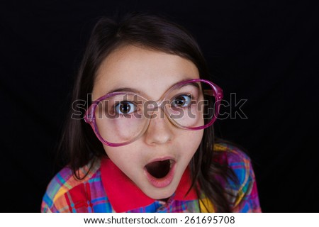 Surprised  little girl with mouth open isolated over black background. - stock photo