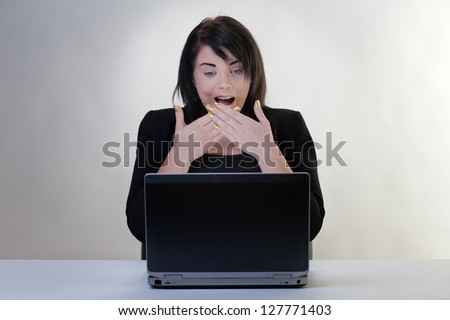 surprised looking woman working at her desk on a laptop computer