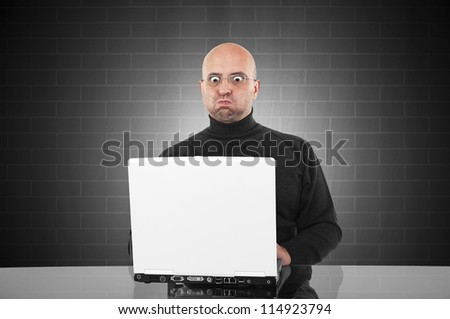 Surprised man blowing his cheeks and looking surprised to the monitor of his laptop - stock photo