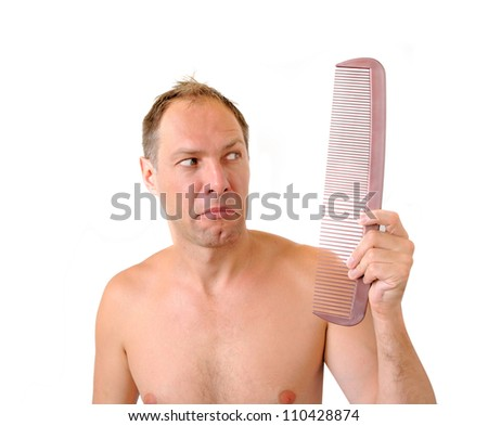 Surprised man hand holding comb near the head - stock photo