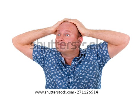 Surprised man in a blue shirt, with big eyes grabbed with both hands behind his head - stock photo