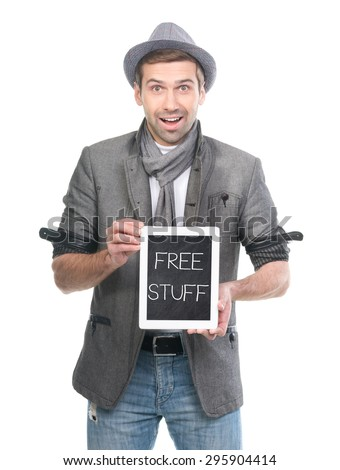 Surprised man in hat with digital tablet pc with FREE STUFF message on a blackboard screen. Isolated. - stock photo