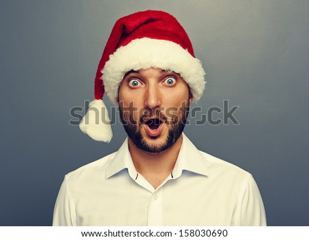 surprised man in red christmas hat over grey background