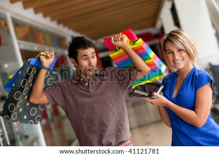 surprised man looking at his empty wallet in a shopping mall