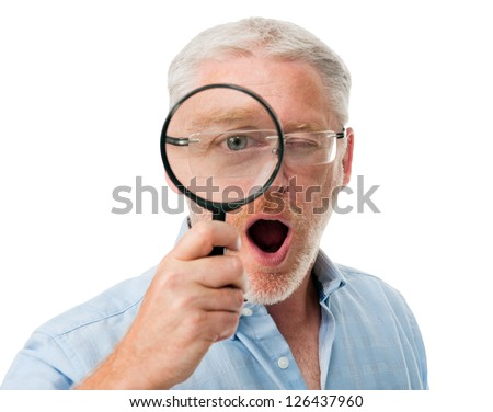 Surprised mature man playing with magnifying glass isolated on white - stock photo