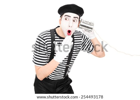 Surprised mime artist listening through a tin can phone isolated on white background - stock photo