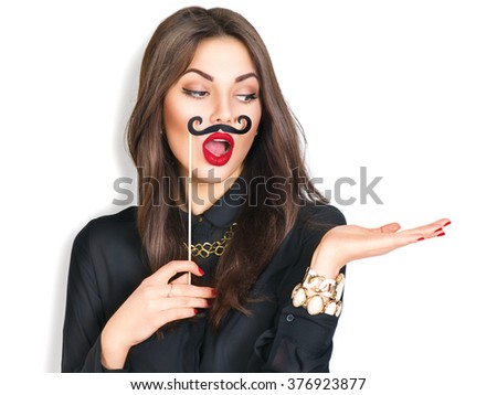 Surprised model Girl holding funny mustache on stick and showing empty copy space on open hand palm for text, white background. Happy girl presenting point. Proposing product. Advertisement gesture