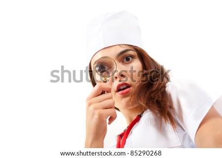 Surprised nurse doing a medical examination. She looks through a magnifying glass - stock photo