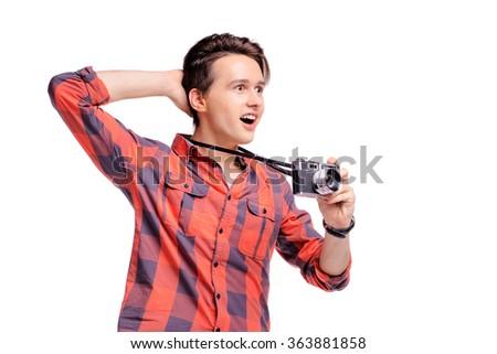 Surprised photographer. Amazed young man in plaid shirt holding retro camera. Isolated on white. - stock photo