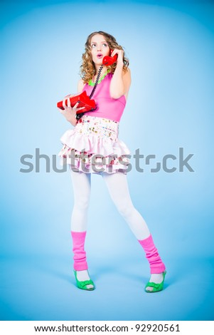 Surprised pin-up woman in colorful clothes standing on the blue background - stock photo
