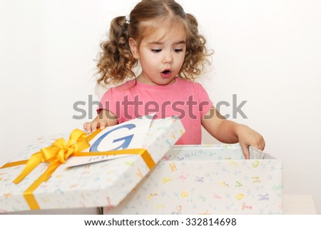 Surprised pretty girl opening the gift box with G letter on it, indoor portrait - stock photo