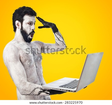 Surprised primitive with laptop over colorful background - stock photo
