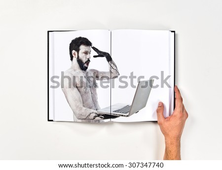 Surprised primitive with laptop printed on book - stock photo