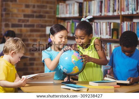 Surprised pupils studying globe in the library in school