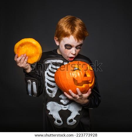 Surprised red haired boy in skeleton costume holding a orange pumpkin. Halloween. Studio portrait over black background - stock photo