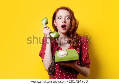 Surprised redhead girl in red polka dot dress with green dial phone on yellow background. - stock photo