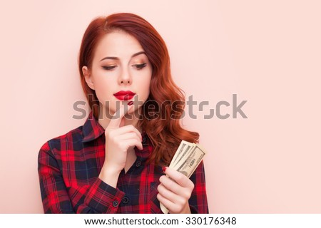 Surprised redhead girl in red tartan dress with money on pink background. - stock photo