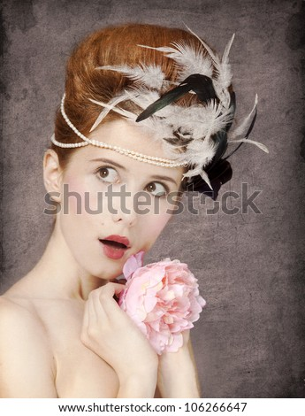 Surprised redhead girl with Rococo hair style and flower at vintage background. Photo in old style.
