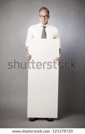 Surprised sad businessman holding white empty vertical billboard with space for text isolated on grey background. - stock photo