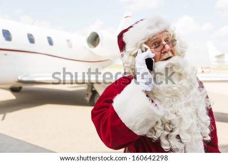 Surprised Santa Claus using mobile phone against private jet at airport terminal - stock photo