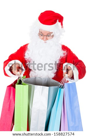 Surprised santa looking inside shopping bag on white background - stock photo