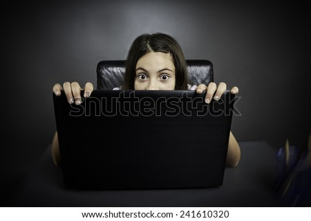 Surprised schoolgirl sitting at her desk hides behind her laptop. - stock photo