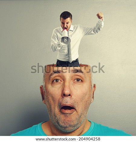 surprised senior man with small angry businessman in his head over grey background - stock photo