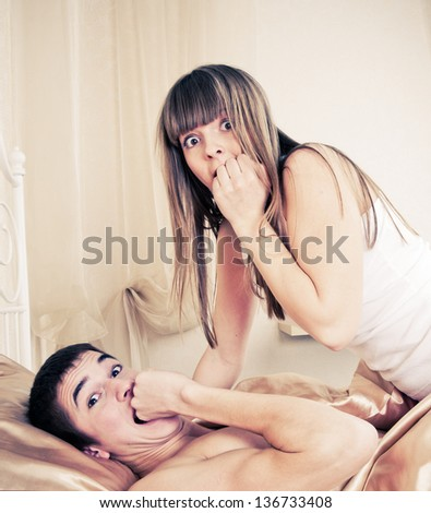 Surprised sex couple lying in bed - stock photo