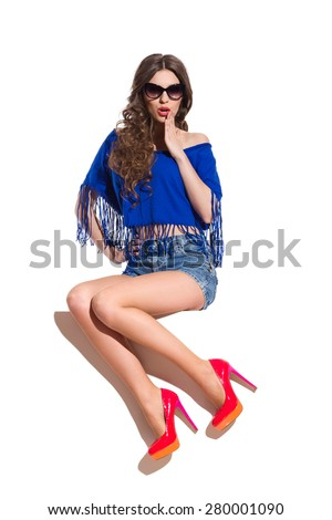 Surprised sexy woman in sunglasses, blue top, jeans shorts and red high heels sitting on the white banner and holding hand on chin. Full length studio shot isolated on white. - stock photo