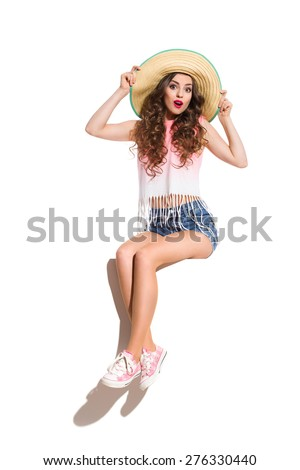 Surprised sexy young woman in straw hat, pink top, jeans shorts and pink sneakers sitting on the white banner. Full length studio shot isolated on white. - stock photo