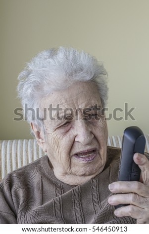 surprised / shocked an elderly woman holding a phone