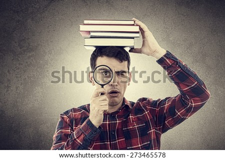 Surprised,Shocked expression of a student young man holding books  on his head and a magnifying glass over grey background. - stock photo