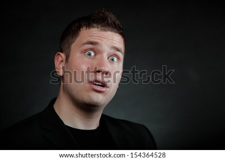 surprised shocked man face wide eyed black background
