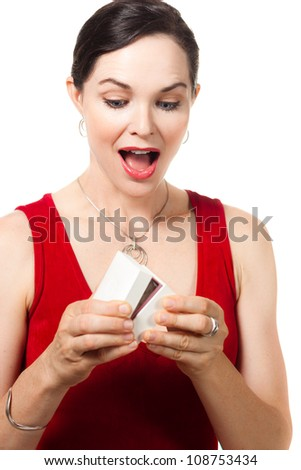 Surprised smiling beautiful woman holding an open jewelery gift box and looking at the present. - stock photo