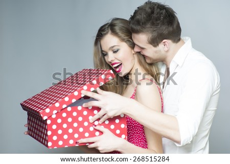 Surprised smiling couple looking into the spotted present box, horizontal picture - stock photo