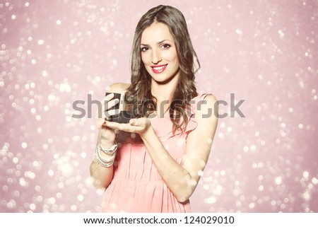 Surprised smiling woman holding an jewelery gift. Romantic atmosphere. - stock photo