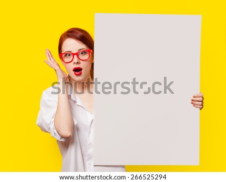 Surprised student girl in white shirt and glasses with white board on yellow background - stock photo