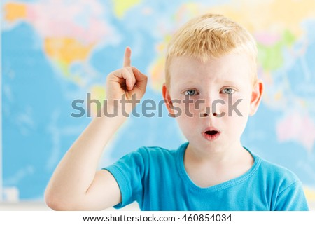 Surprised student raised his finger on geography lesson