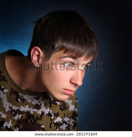 Surprised Teenager in camouflage t-shirt on the Dark Background