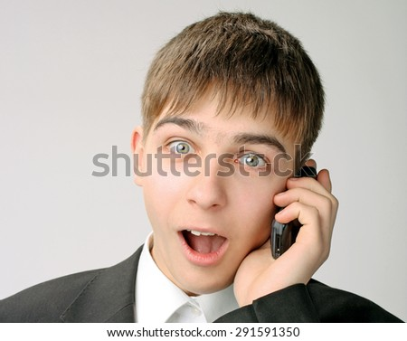 Surprised Teenager with Cellphone on the Gray Background - stock photo