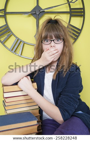 Surprised ten year girl leaning on a stack of books. - stock photo