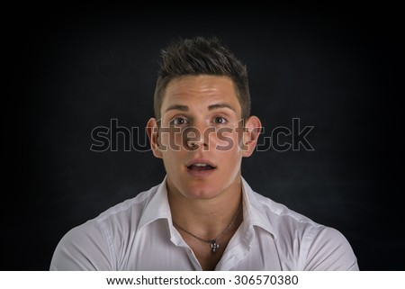 Surprised, unsure handsome young man looking at camera, isolated on black